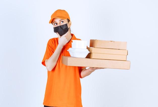 Курьер-женщина в желтой форме и черной маске держит несколько картонных посылок и коробок для еды на вынос и выглядит растерянной и задумчивой.