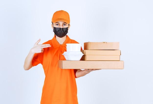 Курьер-женщина в желтой форме и черной маске держит несколько картонных посылок и коробок для еды на вынос, указывая на что-то.