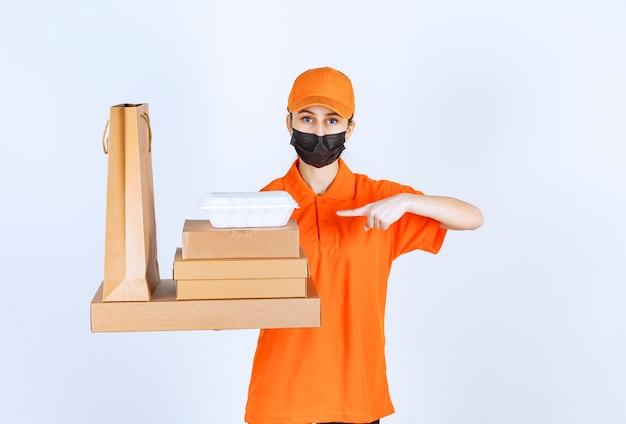 Курьер-женщина в желтой форме и черной маске держит несколько картонных посылок, коробку на вынос и сумку для покупок.