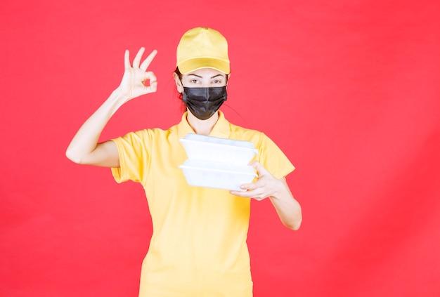 Курьер-женщина в желтой форме и черной маске держит несколько пакетов на вынос и показывает знак рукой