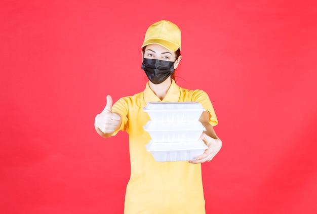 複数の持ち帰り用パッケージを保持し、肯定的な手のサインを示す黄色の制服と黒のマスクの女性の宅配便