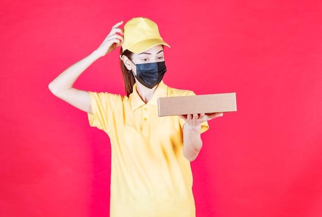 段ボール箱を保持し、思慮深く疑わしいように見える黄色の制服と黒のマスクの女性の宅配便
