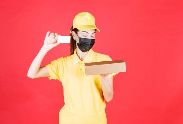 Женский курьер в желтой форме и черной маске держит картонную коробку и представляет свою визитную карточку