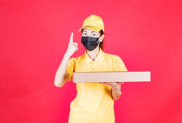 段ボール箱を保持している黄色の制服と黒のマスクの女性の宅配便は混乱して思慮深く見えます