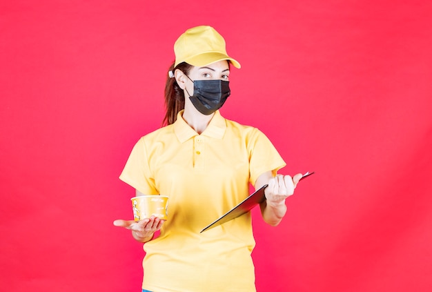 Женский курьер в желтой форме и черной маске доставляет чашку с лапшой и проверяет адрес или имя