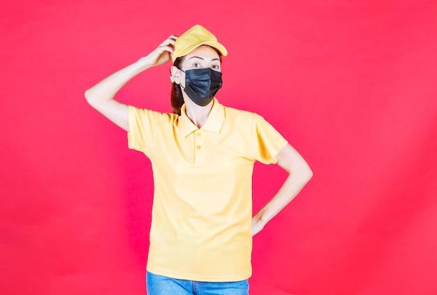 黄色の制服と黒いマスクの女性の宅配便は混乱して思慮深く見えます
