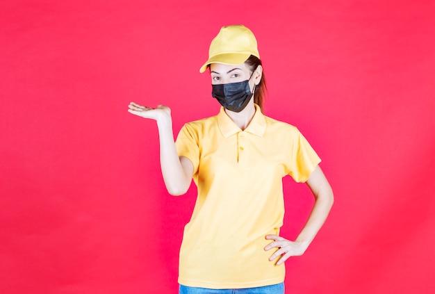 Женский курьер в желтой форме и черной маске, указывая на кого-то