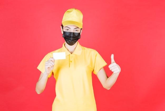 彼女の名刺を提示し、親指を表示している黄色の制服と黒のマスクの女性の宅配便