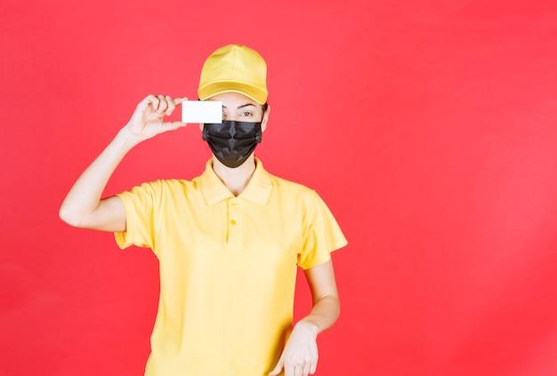 Женский курьер в желтой форме и черной маске, представляя свою визитную карточку