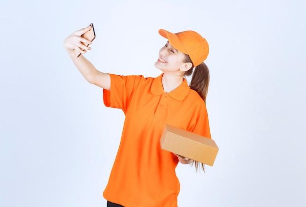 노란색 유니폼을 입은 여성 택배기사가 판지 상자를 배달하고 고객에게 화상 통화를 합니다.