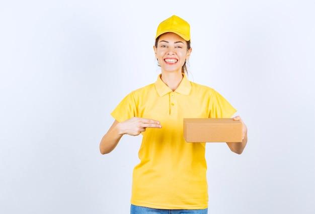노란색 유니폼을 입은 여성 택배가 판지 소포를 배달하고 긍정적인 느낌을 줍니다.