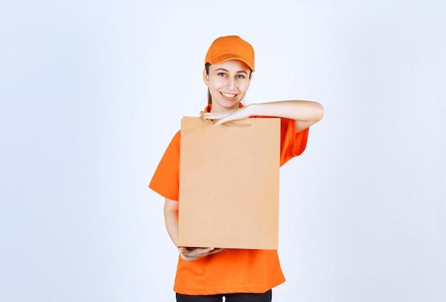 ショッピングバッグを届ける黄色い制服を着た女性の宅配便