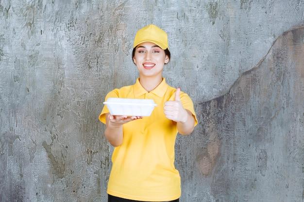 白いテイクアウトボックスを提供し、食べ物を楽しんでいる黄色の制服を着た女性の宅配便