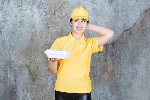 Курьер-женщина в желтой форме доставляет белую коробку для еды и выглядит задумчиво.