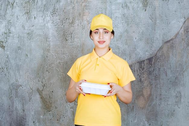 白い持ち帰り用の箱を届ける黄色い制服を着た女性の宅配便