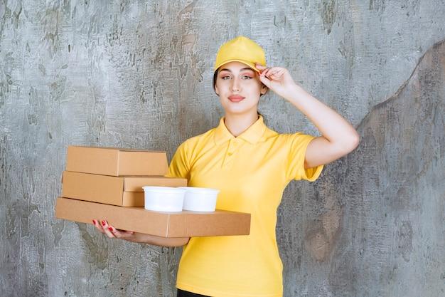Курьер-женщина в желтой форме доставляет несколько картонных коробок и стаканчиков на вынос.
