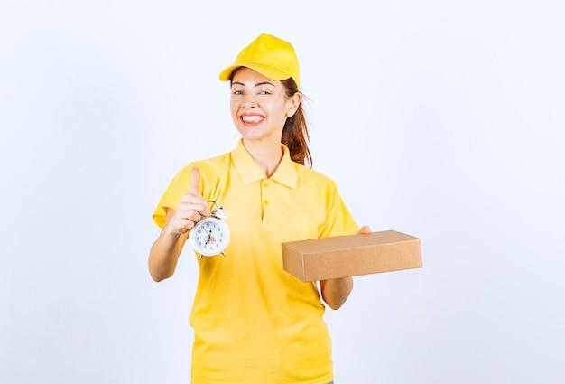 Женский курьер в желтой форме держит картонную коробку и будильник, что означает своевременную экспресс-доставку.
