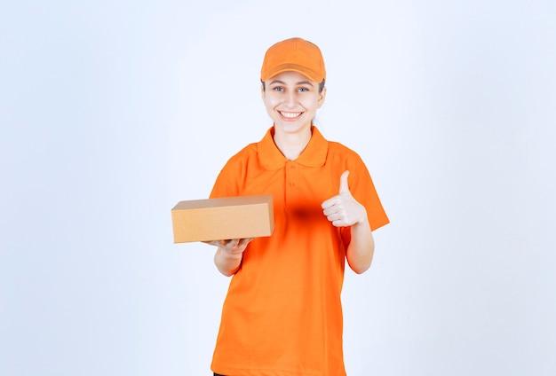 Женский курьер в желтой форме держит картонную коробку и показывает положительный знак рукой.