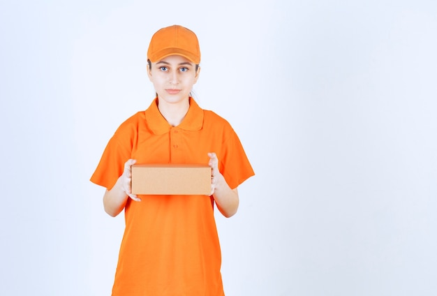Женский курьер в желтой форме держит картонную коробку.