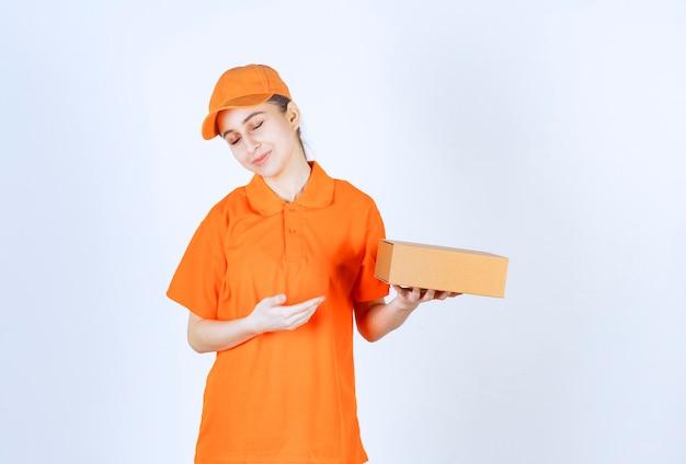 段ボール箱を保持している黄色の制服を着た女性の宅配便