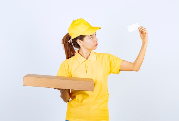 段ボールの小包を保持し、彼女の名刺を提示する黄色の制服を着た女性の宅配便。