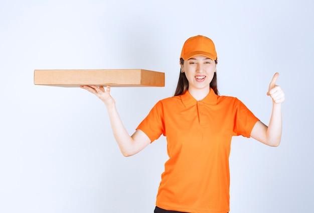 Женский курьер в желтой форме держит картонную коробку на вынос и показывает знак рукой удовольствия.