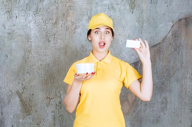 Женский курьер в желтой форме держит чашку на вынос и представляет свою визитную карточку.