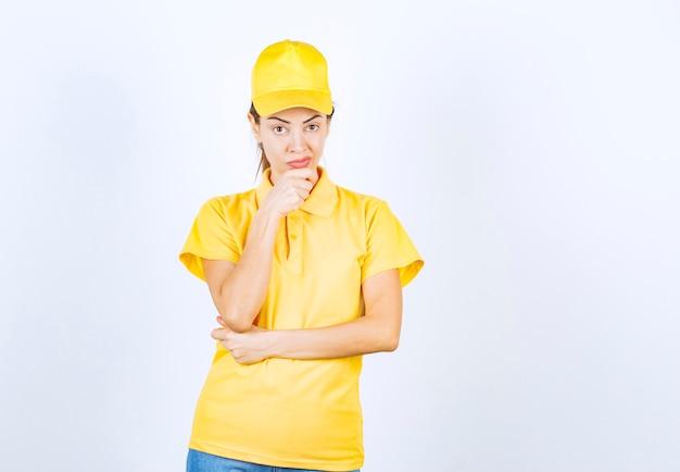 黄色い制服を着た女性の宅配便は思慮深く見えます。