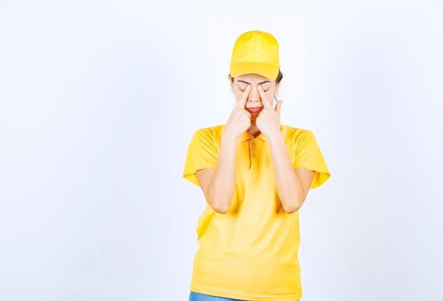 노란색 제복을 입은 여성 택배는 피곤하고 졸려 보입니다.