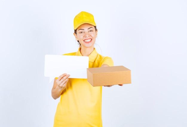 Курьер женского пола в желтой форме, предлагающий заказ покупателю и предъявляющий сертификат подлинности.