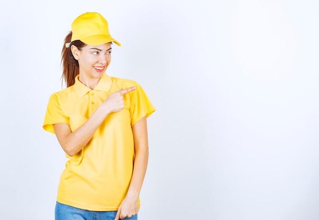 どこかを指している黄色い制服を着た女性の宅配便。