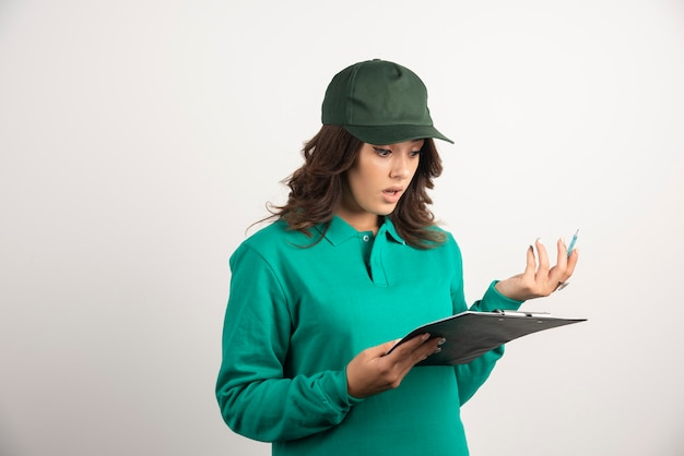Female courier looking at clipboard shockingly.