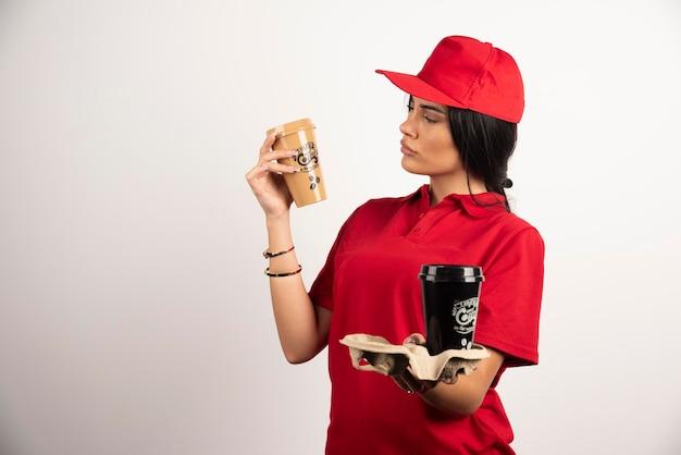 Corriere femminile che esamina tazza di caffè. foto di alta qualità