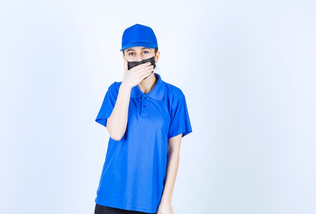 Female courier in mask and blue uniform closing mouth and asking for silence.