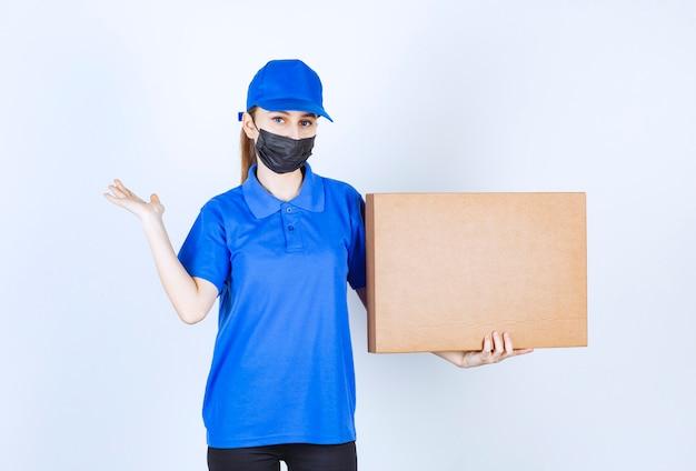 Corriere femminile in maschera e uniforme blu che tiene un grosso pacco di cartone e indica qualcuno