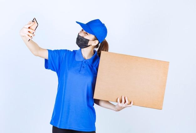 Corriere femminile in maschera e uniforme blu che tiene un grosso pacco di cartone e prende nuovi ordini al telefono