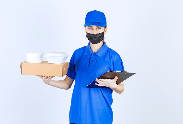 Female courier in mask and blue uniform holding a cardboard box, takeaway packages and a black folder.
