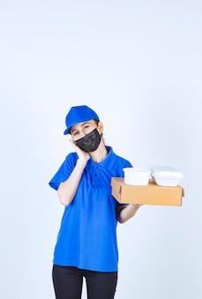 Corriere femminile in maschera e uniforme blu che tiene una scatola di cartone e pacchi da asporto e sembra assonnato e stanco