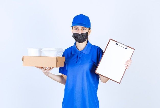 Female courier in mask and blue uniform holding a cardboard box, takeaway packages and presenting the checklist for signature.