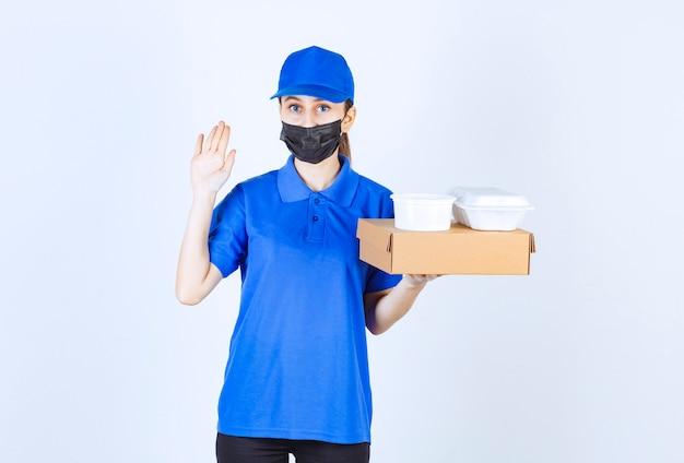 Corriere femminile in maschera e uniforme blu che tiene una scatola di cartone e pacchi da asporto e ferma qualcuno.
