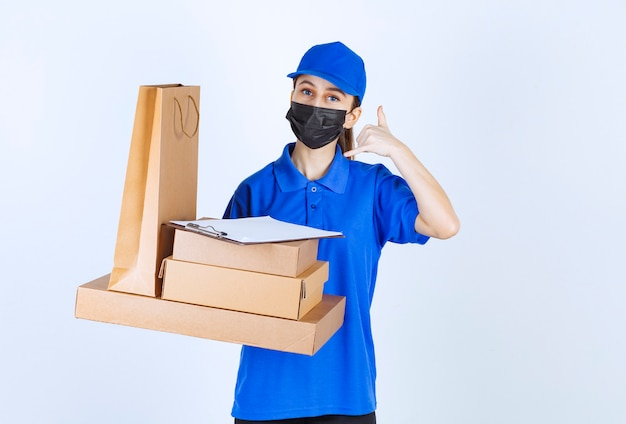 Female courier in mask and blue uniform holding a cardboard shopping bag and multiple boxes while asking for a call.