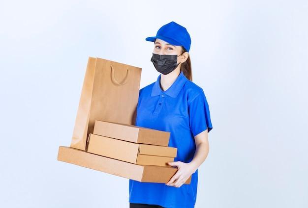 Corriere femminile in maschera e uniforme blu che tiene una borsa della spesa in cartone e scatole multiple.