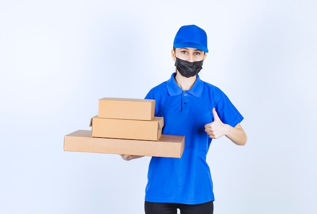 Female courier in mask and blue uniform holding a stock of cardboard boxes and showing positive hand sign