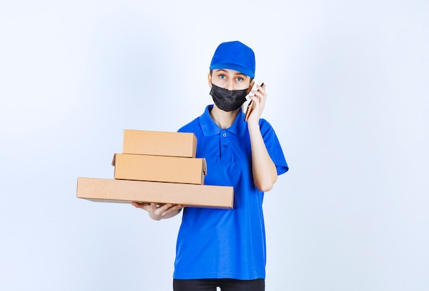 Female courier in mask and blue uniform holding a stock of cardboard boxes and talking to the phone.