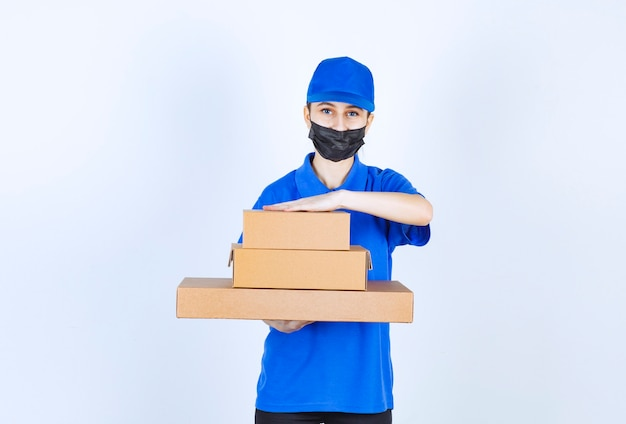 Female courier in mask and blue uniform holding a stock of cardboard boxes.