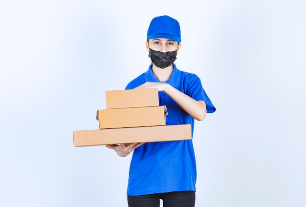 Female courier in mask and blue uniform holding a stock of cardboard boxes