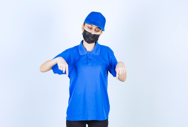 Female courier in mask and blue uniform showing something below