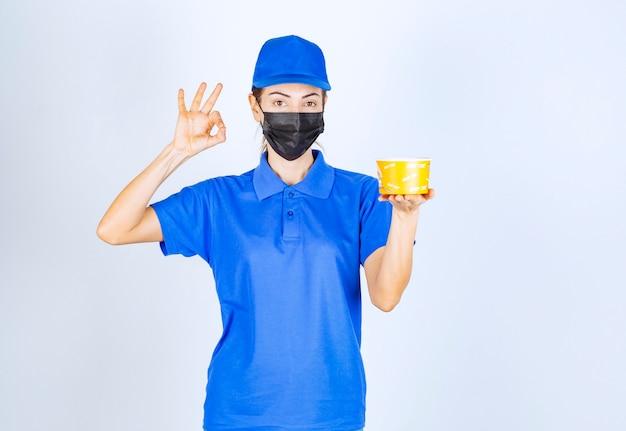 青いユニフォームとフェイスマスクを身に着けたレストランの女性宅配便は、持ち帰り用の食べ物を提供し、美味しさを保証します。