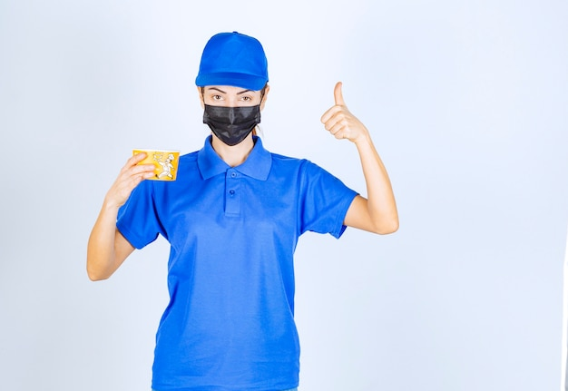 파란색 유니폼과 마스크를 쓴 식당의 여성 택배기사가 테이크아웃 음식을 배달하며 좋은 맛을 보장한다.