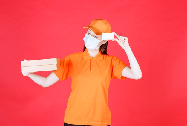 Female courier in orange color dresscode and mask holding a cardboard box and presenting her business card.